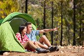Camping couple in tent sitting looking at view in forest. Campers smiling happy outdoors in forest p