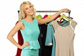 Smiling blond woman choosing clothes on a rack