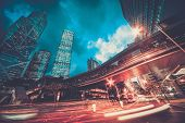 stock photo of skyscrapers  - Fast moving cars at night in modern city - JPG
