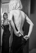 stock photo of manor  - Young beautiful luxurious woman zipping up her long elegant black dress looking in a large mirror - JPG