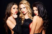 pic of seduction  - Three beautiful enticing glamorous woman posing together on a dark background looking seductively at the camera with sultry thoughtful expressions - JPG
