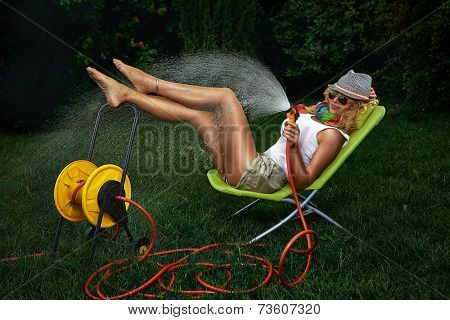 Beautiful woman having fun with garden hose splashing summer rain.