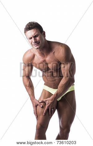 Muscular Man In Underwear Holding His Leg In Pain