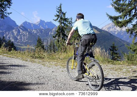 Man Is Cycling In The Alps