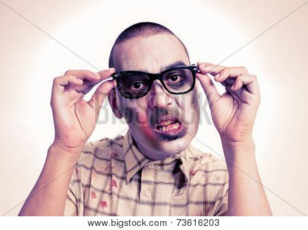 portrait of a hipster zombie putting on his black plastic-rimmed eyeglasses