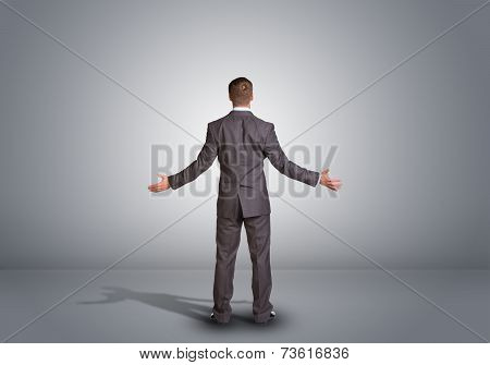 Businessman standing in an empty gray room. Rear view