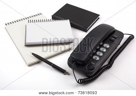 Black phone and notebooks on white background.