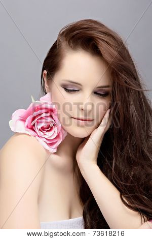 Portrait of a beautiful young brunette woman. Wearing long loose curly hair, posing with a pink flower. Against grey studio background. Spa concept
