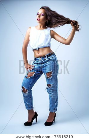 beautiful young brunette model wearing torn jeans, studio shot