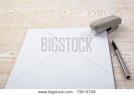 Sheets of paper and office accessories on wooden texture.