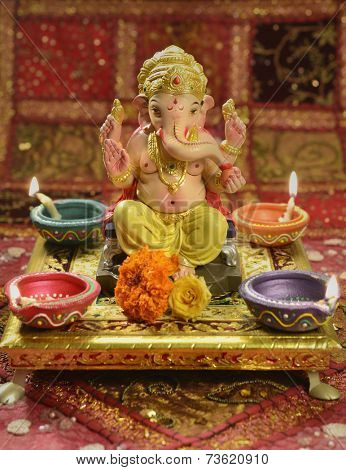 A statue of a mythological elephant god -Ganesha, surrounded by traditional divali lamps