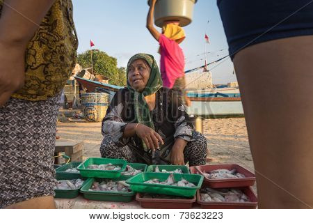 BALI, INDONESIA - SEPTEMBER 20, 2014: Fish-mongers wait for customers at an open market on Jimbaran Beach. Fishery is an important traditional industry on Bali Island.