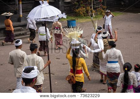 BALI, INDONESIA - SEPTEMBER 20, 2014: Hindu devotees brings the cremated remains of a family member placed inside the white cloth for the Nyaben 11th day prayers at the Besakih Temple Complex.