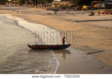 BALI, INDONESIA - SEPTEMBER 20, 2014: A fisherman returning to shore at Jimbaran fishing village in a traditional Balinese fishing boat. Fishery is an important traditional industry on Bali Island.