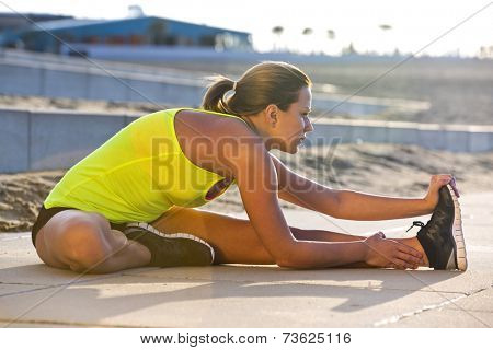Athletic woman stretching her hamstrings on a beach during a training run on a warm, summer evening.