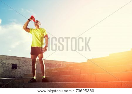 Dark-skinned runner drink water after intensive evening run