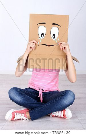 Woman with cardboard box on her head with sad face, near wall
