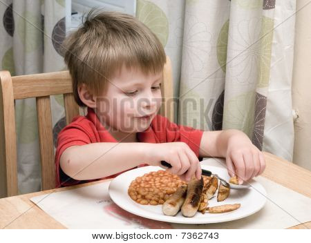 Little boy eating typical english meal.