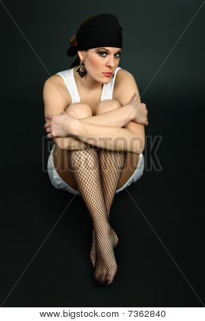 Sexy girl sitting on floor wearing fish net stockings and headscarf