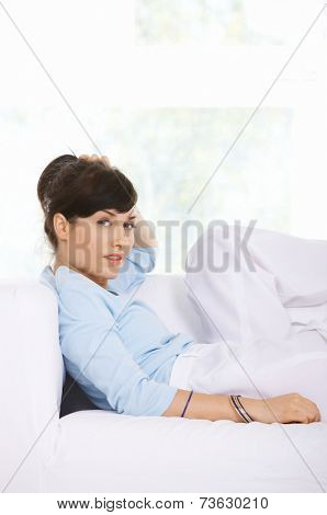 High key portrait of a stylish attractive young woman relaxing on a sofa   side view looking at the camera