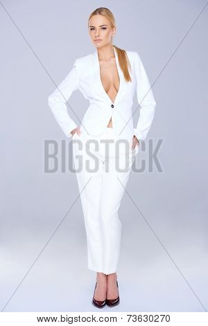Stylish slender woman in a white slack suit with no shirt displaying her cleavage standing giving the camera a seductive look