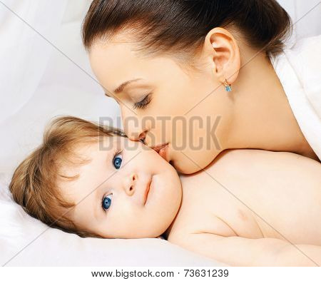 Happy Mom Kissing Baby In Bed
