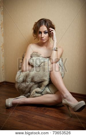 Attractive sexy young woman wrapped in a fur coat sitting on the floor in hotel room
