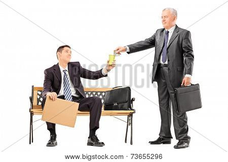 Mature businessman giving some money to a beggar isolated on white background