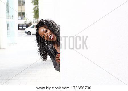 Playful Young Woman Peeking Around A Pillar