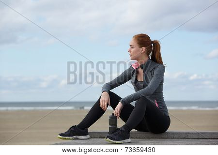 Attractive Sports Woman Relaxing By The Beach After Workout