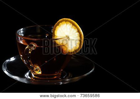 tea in cup with lemon on black background