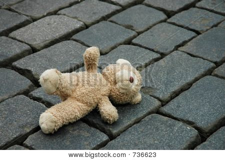 Little teddy-bear laying on the cobblestone pavement