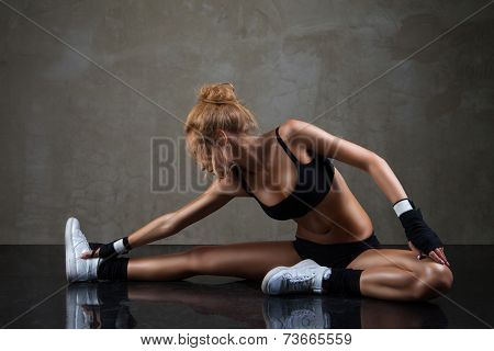 Fit woman stretching her leg over dark background