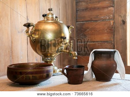 Old Samovar And Ceramic Dishes On A Table In A Country House