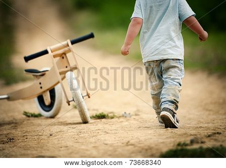 Little boy with tricycle in nature