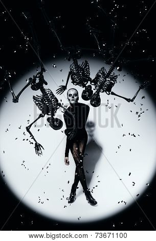 Woman In Skull Make-up And Black Skeletons