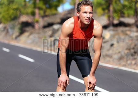 Runner resting after running. Jogging man taking a break during training outdoors in on mountain road. Young Caucasian male fitness model after work out.