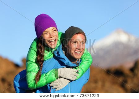 Couple piggyback happy in active lifestyle having fun on hike. Fresh young joyful interracial couple. Asian woman hiker and Caucasian man in outdoor activity on Teide, Tenerife, Canary Islands, Spain