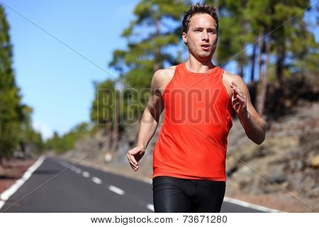 Sprinting runner man running at fast speed. Male sport sprinter training hard. Young strong male fitness model during run outdoors in beautiful landscape.