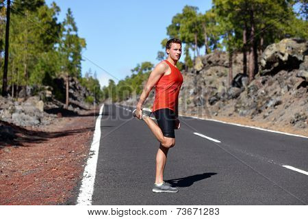 Runner man stretching thigh and legs after running on mountain forest road in. Handsome Caucasian male fitness model outdoors.