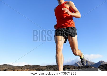 Runner man closeup - male athlete running on road sprinting. Unrecognizable person under blue sky.