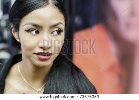 Beautiful young woman turns her head eyes wide open while she shops in mall