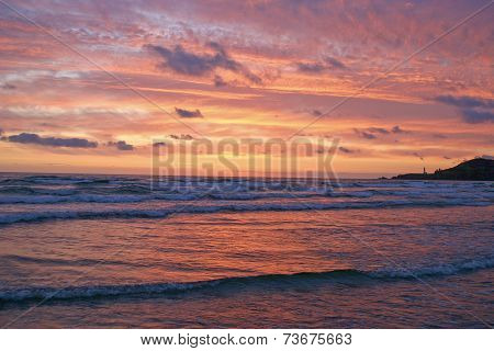 Brilliant Coastal Sunset With Distant Lighthouse