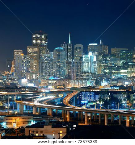 San Francisco city skyline with urban architectures at night with highway bridge.