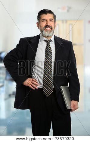 Portrait of senior Hispanic businessman holding laptop inside office building