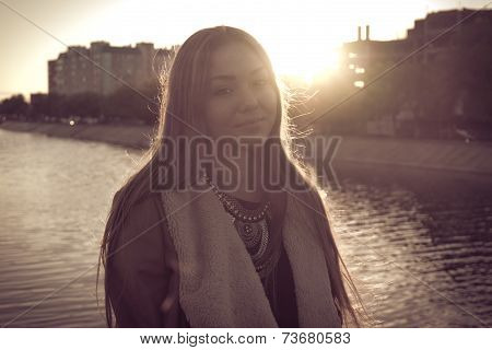 oung fashion woman with handbag in autumn, retro portrait of a beautiful girl against water, instagr
