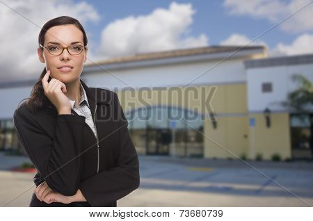Attractive Serious Mixed Race Woman In Front of Vacant Commercial Retail Building.