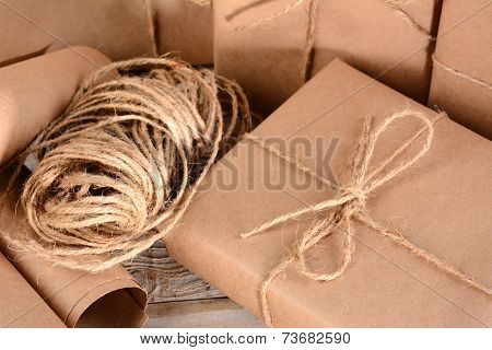 Closeup of a group of packages wrapped with plain brown paper and twine. Horizontal format on a wood table.