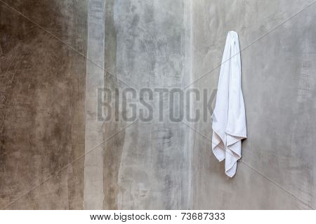 White Towel Is Hanging On The Exposed Concrete Wall In The Bathroom.