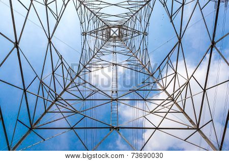 In The Center Of High Voltage Power Pole And Clear Blue Sky Background.